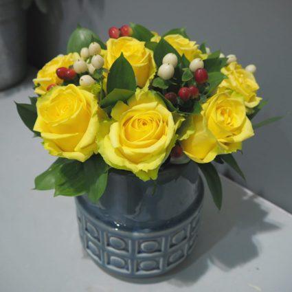 Яркая солнечная композиция из 11 желтых роз в керамической вазе.